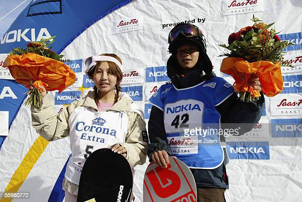 Melo Imai of Japan and Kazuhiro Kokubo of Japan both celebrate victory on the podium during the FIS World Cup Snowboard Halfpipe event on October 21...