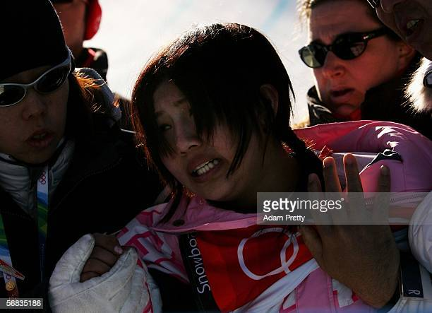 Melo Imai of Japan is helped after falling in the Womens Snowboard Half Pipe Qualifying on Day 3 of the 2006 Turin Winter Olympic Games on February...