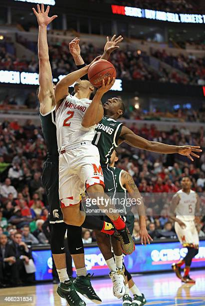 Melo Trimble of the Maryland Terrapins goes up for a shot against Gavin Schilling and Lourawls Nairn Jr #11 of the Michigan State Spartans during the...