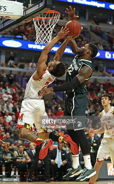 Melo Trimble of the Maryland Terrapins shoots under pressure from Branden Dawson of the Michigan State Spartans during the semifinal round of the...