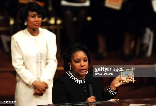 Melodie Cochran listens as her sister Tiffany Cochran Edwards holding a photograph of her father in a Hercules pose speaks during the funeral service...