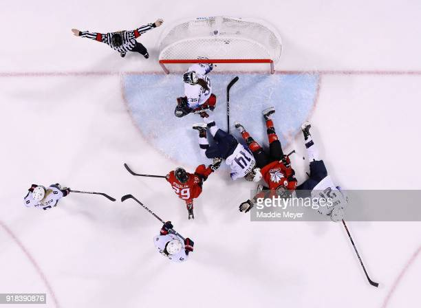 Melodie Daoust of Canada and Hilary Knight of the United States and Brianna Decker of the United States get knocked down in the first period during...