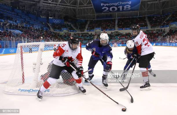 Melodie Daoust of Canada controls the puck against Megan Keller of the United States in overtime during the Women's Gold Medal Game on day thirteen...