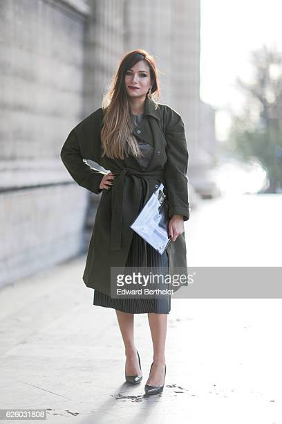 Melody Bernard is wearing a Collection IRL x ShowroomPrive outfit made of a green cargo trench coat a black skirt a gray tshirt with the inscription...