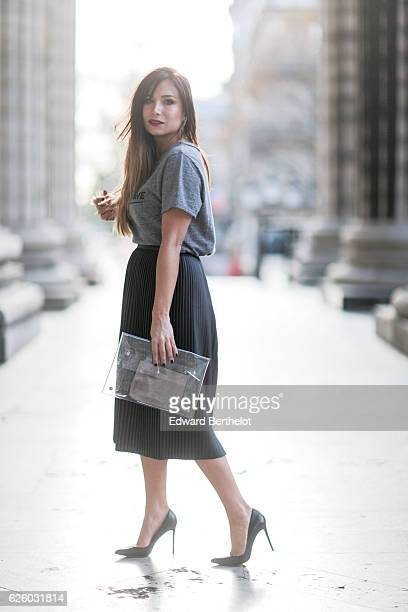 Melody Bernard is wearing a Collection IRL x ShowroomPrive outfit made of a black skirt a gray tshirt with the inscription 'C'est Pas Grave' Mango...