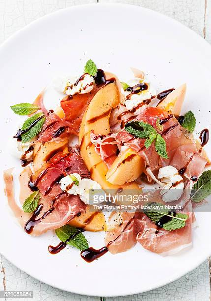 Melon and prosciutto ham salad with Mozzarella and mint leaves