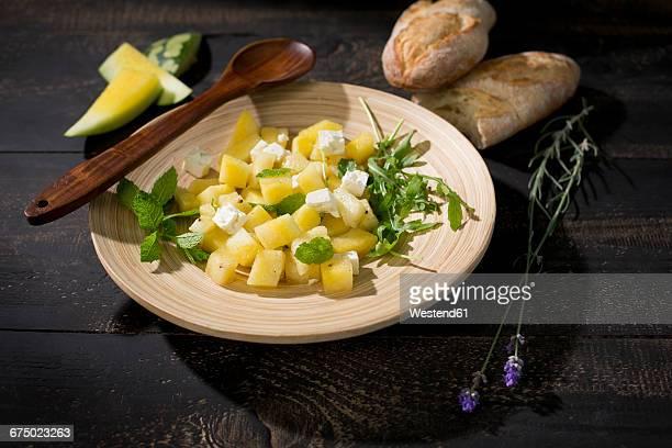 Melon salad, yellow watermelon, feta, mint and rocket on plate