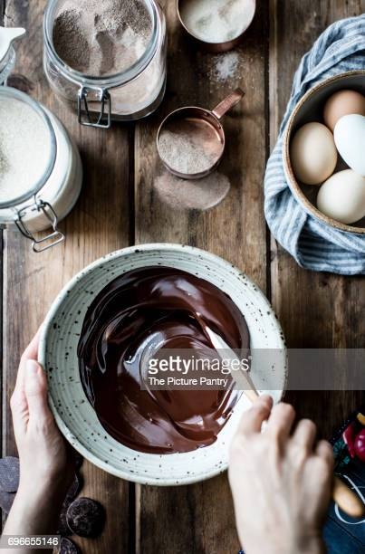 Melted chocolate frosting being stirred in a mixing bowl