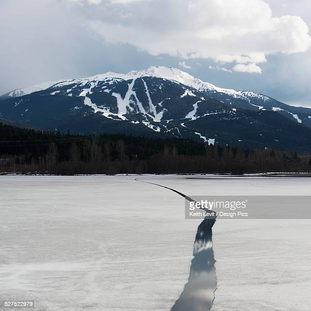 A melted crack in the frozen lake with snowcapped mountains in the distance