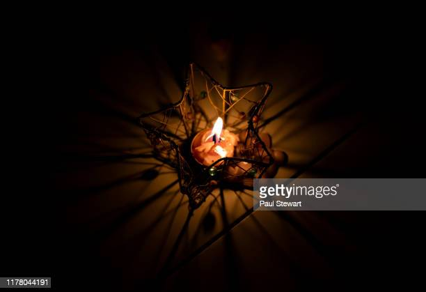 melted lit up candle in the dark - candle in the dark stock pictures, royalty-free photos & images