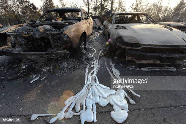 Melted metal from burnt cars is formed on the ground after wildfires ripped through the Coffey Park neighborhood of Santa Rosa California on October...