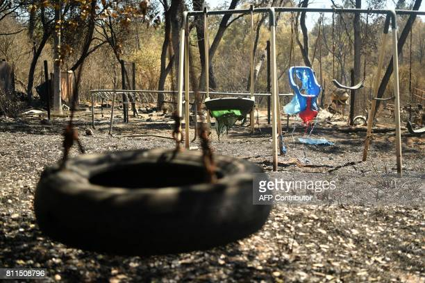 A melted swing set is seen along a burned out residential property after the Wall fire tore through the area and burned dozens of homes and...