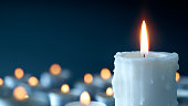 Melting candle on cool blue background