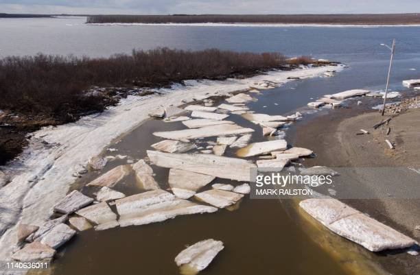Melting ice beside severe erosion of the permafrost tundra at Bethel on the Yukon Delta in Alaska on April 15, 2019. - According to scientists,...