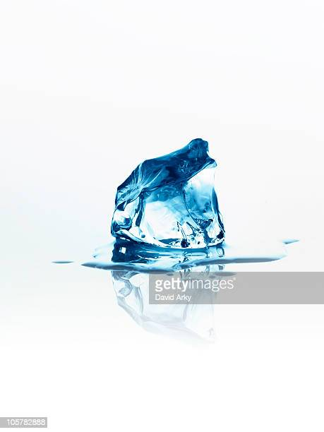 melting ice cube - puddle stock pictures, royalty-free photos & images