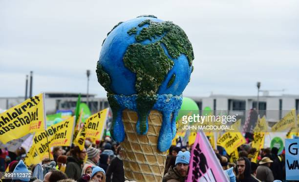 """Melting planet in an ice cone is held up during the """"Global Climate March"""" that is organised by environmental NGOs on November 29, 2015 in Berlin on..."""