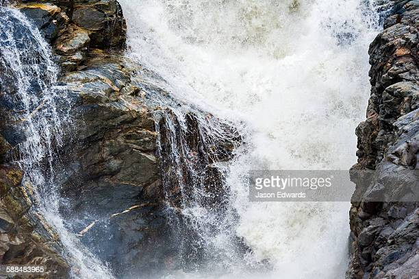 Meltwater floods a cascading waterfall at the base of a glacier.