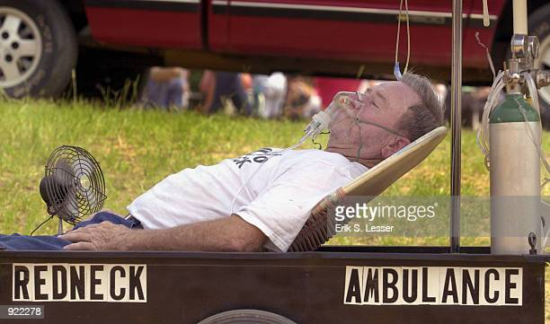 Melvin Davis takes a breather during the Seventh Annual Summer Redneck Games July 6, 2002 in East Dublin, Georgia. Thousands of people flock to the...