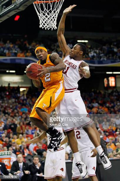 Melvin Goins of the Tennessee Volunteers goes up for a shot against Delvon Johnson of the Arkansas Razorbacks during the first round of the SEC Men's...