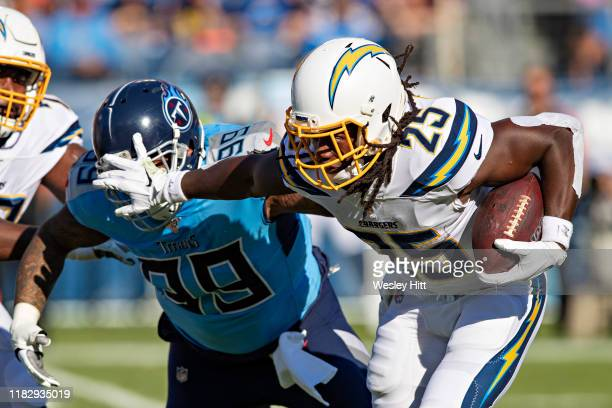 Melvin Gordon III of the Los Angeles Chargers runs the ball and stiff arms Jurrell Casey of the Tennessee Titans at Nissan Stadium on October 20,...