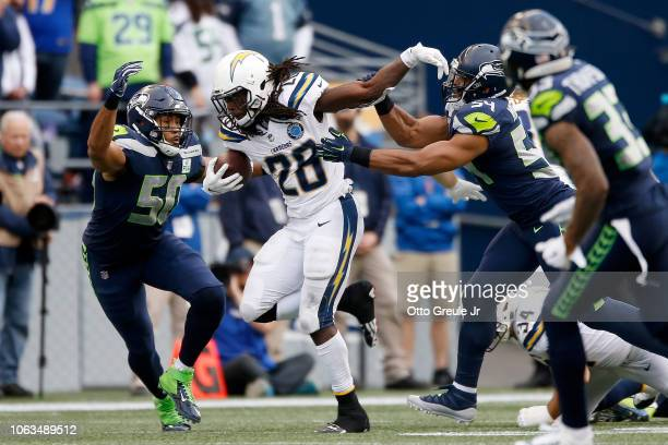 Melvin Gordon III of the Los Angeles Chargers runs with the ball while being chased by KJ Wright and Bobby Wagner of the Seattle Seahawks in the...
