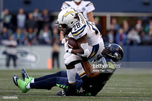 Melvin Gordon III of the Los Angeles Chargers runs with the ball while being tackled by KJ Wright of the Seattle Seahawks in the fourth quarter at...