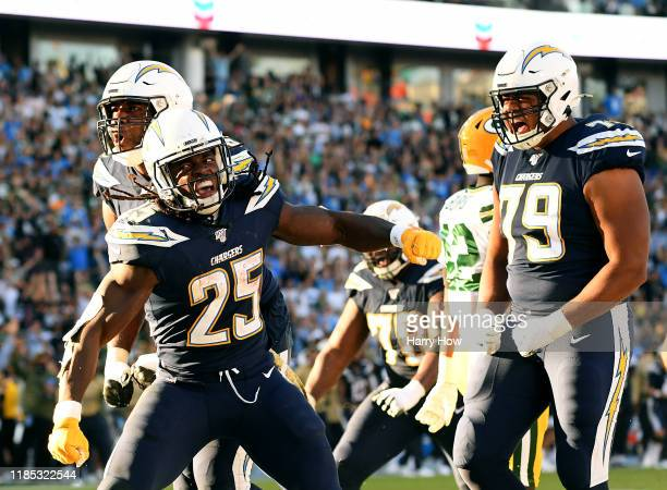 Melvin Gordon of the Los Angeles Chargers celebrates his touchdown with Russell Okung and Trey Pipkins, to take a 26-3 lead, during the fourth...
