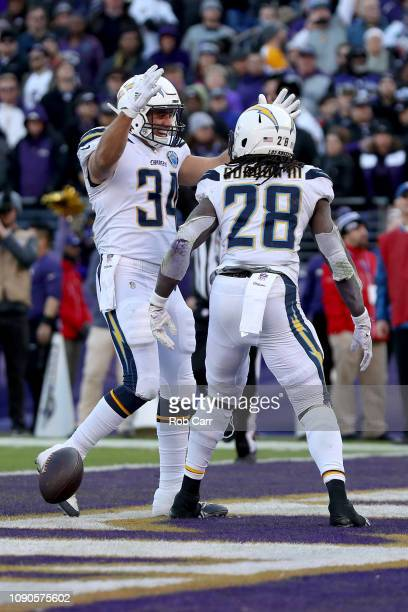 Melvin Gordon of the Los Angeles Chargers celebrates with Derek Watt after scoring a one yard touchdown against the Baltimore Ravens during the...