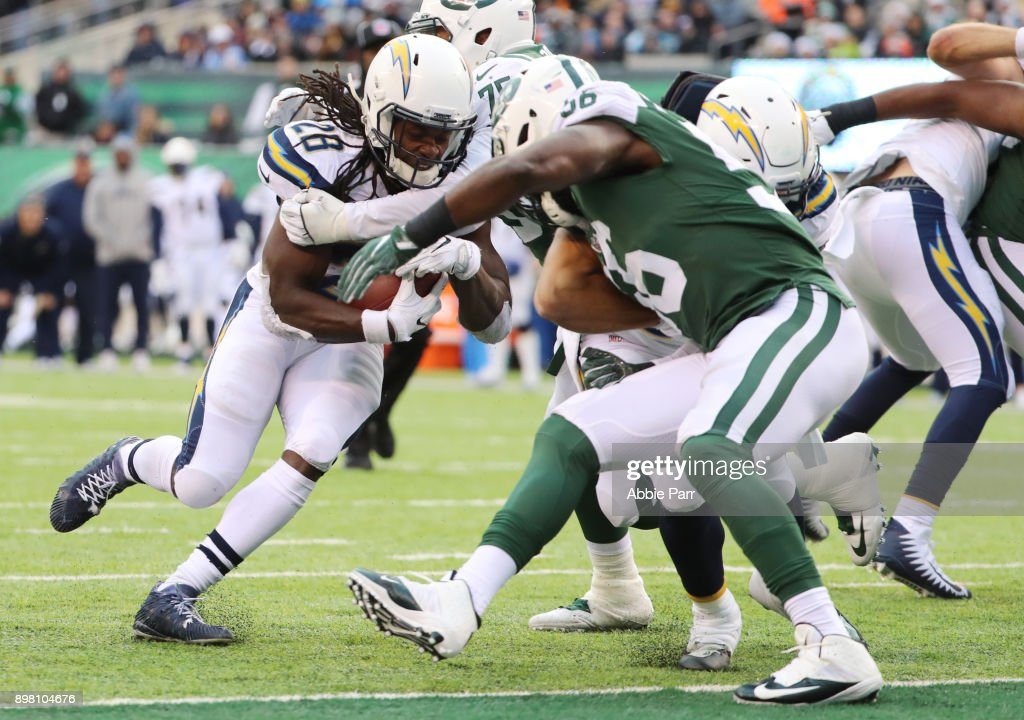 Melvin Gordon #28 of the Los Angeles Chargers dives across the goaline for a rushing touchdown against Demario Davis #56 of the New York Jets during the second half of an NFL game at MetLife Stadium on December 24, 2017 in East Rutherford, New Jersey.