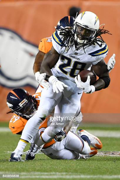 Melvin Gordon of the Los Angeles Chargers is tackled by Brandon Marshall of the Denver Broncos and Bradley Roby during the fourth quarter on Monday...