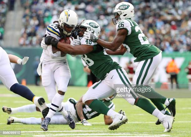 Melvin Gordon of the Los Angeles Chargers is tackled by Jordan Jenkins and Marcus Maye of the New York Jets during the first half of an NFL game at...
