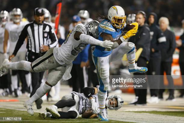 Melvin Gordon of the Los Angeles Chargers is tackled by Tahir Whitehead of the Oakland Raiders in the second quarter at RingCentral Coliseum on...