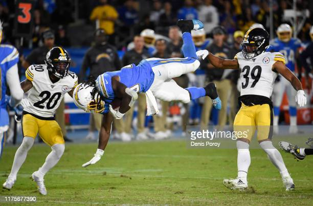 Melvin Gordon of the Los Angeles Chargers is upended by Minkah Fitzpatrick of the Pittsburgh Steelers on a pass reception in the second quarter at...