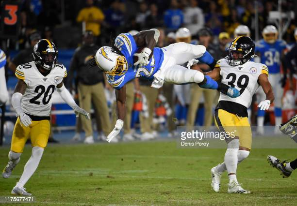 Melvin Gordon of the Los Angeles Chargers is upended by Minkah Fitzpatrick of the Pittsburgh Steelers on a pass reception during the second quarter...