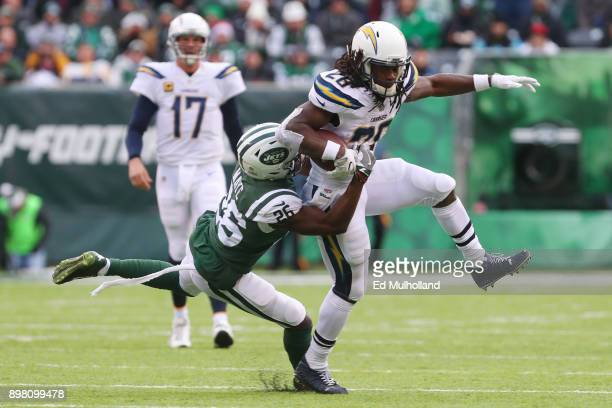 Melvin Gordon of the Los Angeles Chargers is wrapped up by Marcus Maye of the New York Jets during the first half of an NFL game at MetLife Stadium...