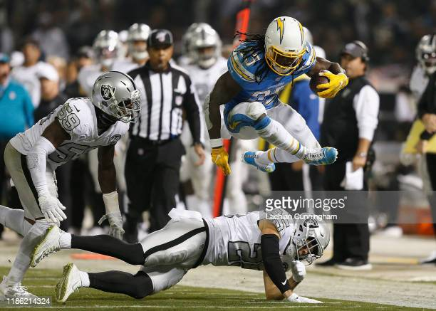 Melvin Gordon of the Los Angeles Chargers jumps over Erik Harris of the Oakland Raiders in the second quarter at RingCentral Coliseum on November 07...