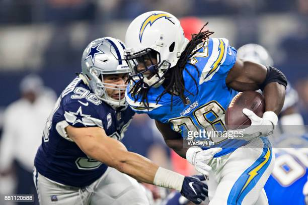 Melvin Gordon of the Los Angeles Chargers runs the ball and is hit by Tyrone Crawford of the Dallas Cowboys at AT&T Stadium on November 23, 2017 in...
