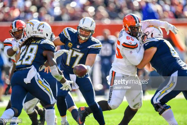 Melvin Gordon of the Los Angeles Chargers takes a hand off from Philip Rivers during the game against the Cleveland Browns at FirstEnergy Stadium on...