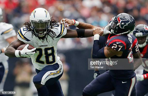 Melvin Gordon of the San Diego Chargers gives a stiff arm to Quintin Demps of the Houston Texans in the second quarter at NRG Stadium on November 27,...