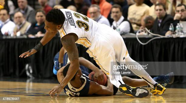 Melvin Johnson of the Virginia Commonwealth Rams falls over Nick Griffin of the George Washington Colonials in the first half with an injury during...