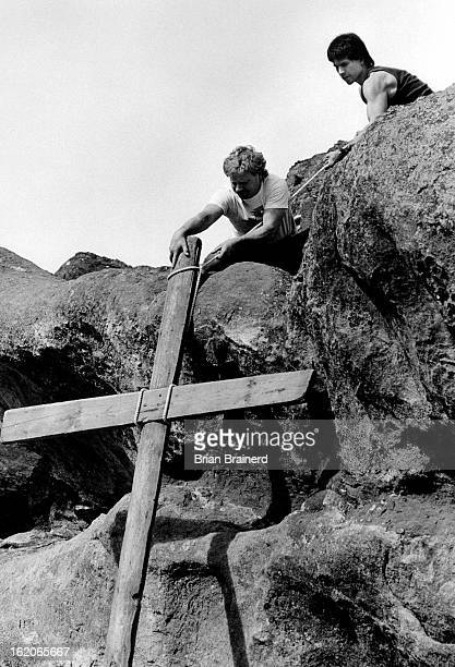 APR 19 1987 Melvin Reams and Charles Elliott haul up one of three crosses in preparation for Sunday's sunrise Easter service at Red Rocks...