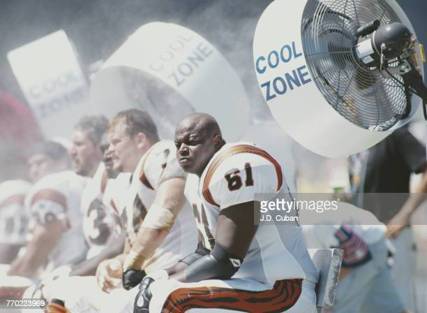 Melvin Tuten Center for the Cincinnati Bengals sits on the bench to keep cool by the large air conditioning cooling fans during the American Football...