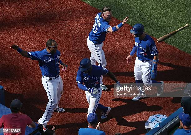 Melvin Upton Jr #7 of the Toronto Blue Jays is congratulated by Edwin Encarnacion after hitting a tworun insidethepark home run as Josh Donaldson...