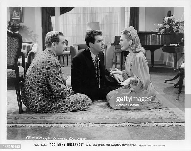 Melvyn Douglas and Fred MacMurray sitting on the carpet with Jean Arthur in a scene from the film 'Too Many Husbands' 1940