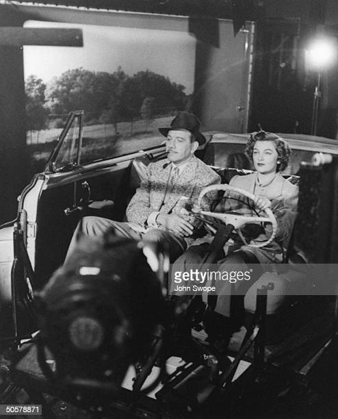 Melvyn Douglas and Myrna Loy being filmed in studio with projected background for Mr Blandings Builds His Dream House