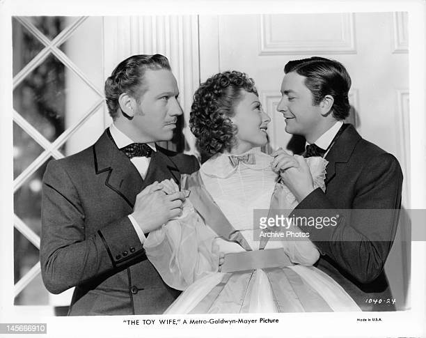 Melvyn Douglas looking angrily as Luise Rainer smiles at Robert Young in a scene from the film 'The Toy Wife' 1938