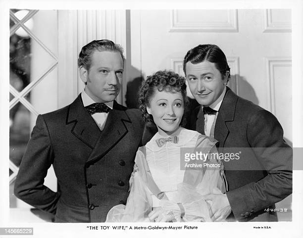 Melvyn Douglas Luise Rainer and Robert Young standing by doorway in a scene from the film 'The Toy Wife' 1938