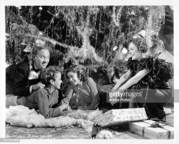 Melvyn Douglas under the Christmas tree looking over two children to see Mary Astor in a scene from the film 'And So They Were Married' 1936