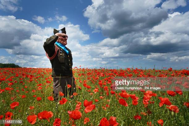 Melvyn Dunn from Ackworth West Yorkshire salutes in a field of poppies after he laid a wreath at the British Normandy Memorial site in VersurMer in...