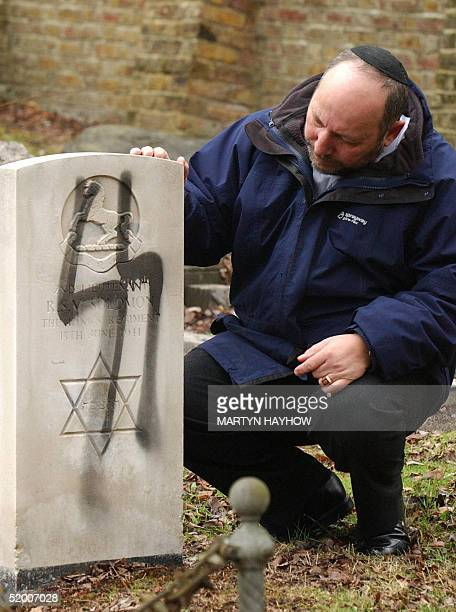 Melvyn Hartog Head of Burial for the United Synagogues of the UK looks at a military grave that was vandalized with the Nazi SS logo at the Jewish...